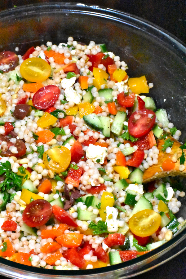 israeli couscous salad in a clear bowl