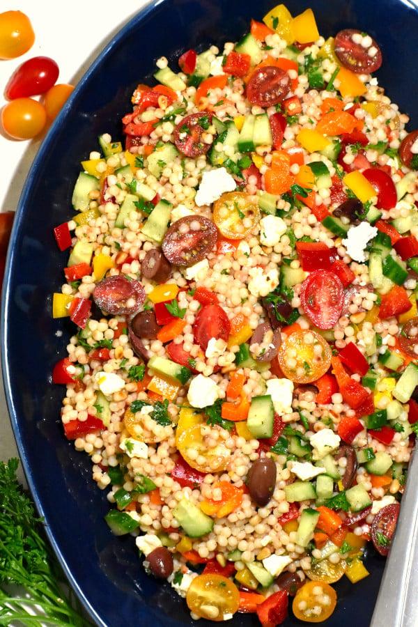 israeli couscous salad on a blue platter