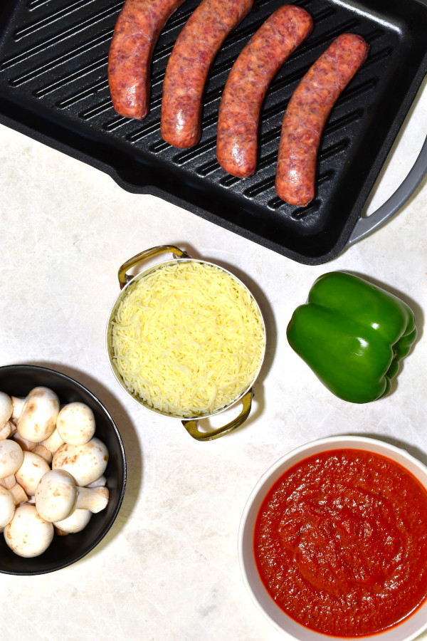 four italian sausages, a green bell pepper, mushrooms, mozzarella cheese and marinara sauce on a white background