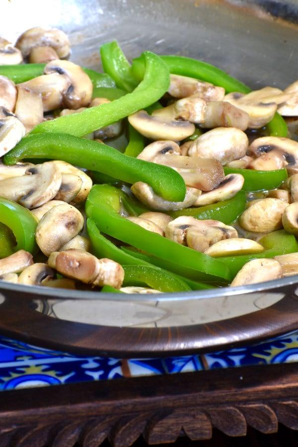 cut mushrooms and greenn pepper in a frying pan