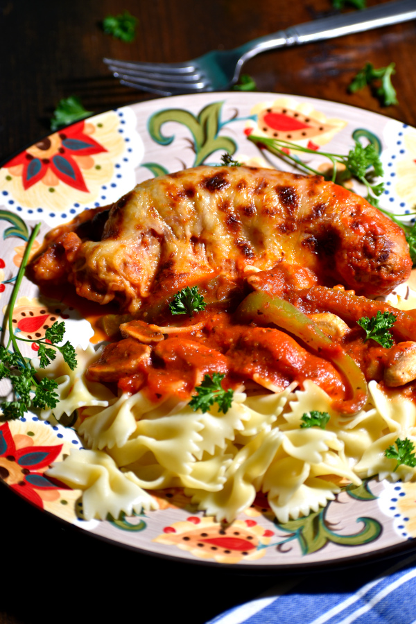 serving of italian sausage bake on the gypsy plate alongside some bowtie pasta