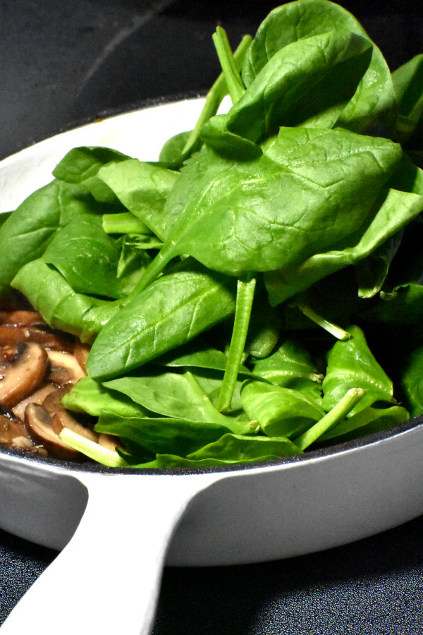 spinach added to cooked mushromms in a skillet
