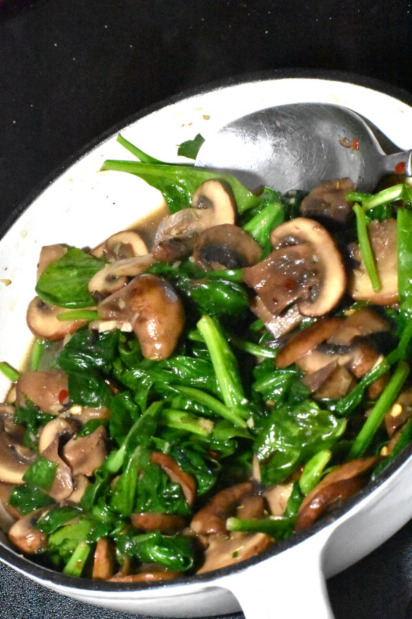 cooked mushrooms and spinach in a small skillet