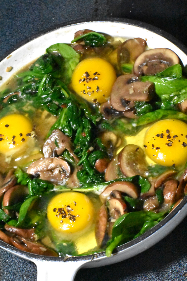 raw eggs added to cooked muchrooms and spinach