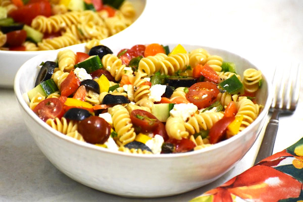 rainbow pasta salad in a white bowl with another in the background