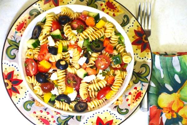 rainbow pasta salad in a white bowl atop the gypsy plate
