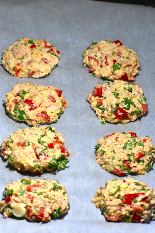 eight salmon patties, uncooked, on a platter
