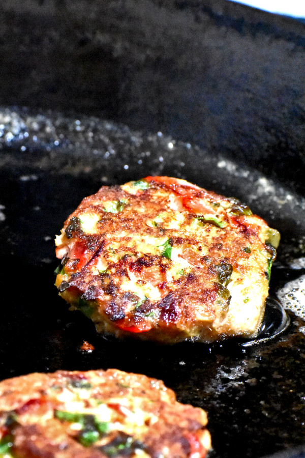 salmon patty frying in a cast iron skillet