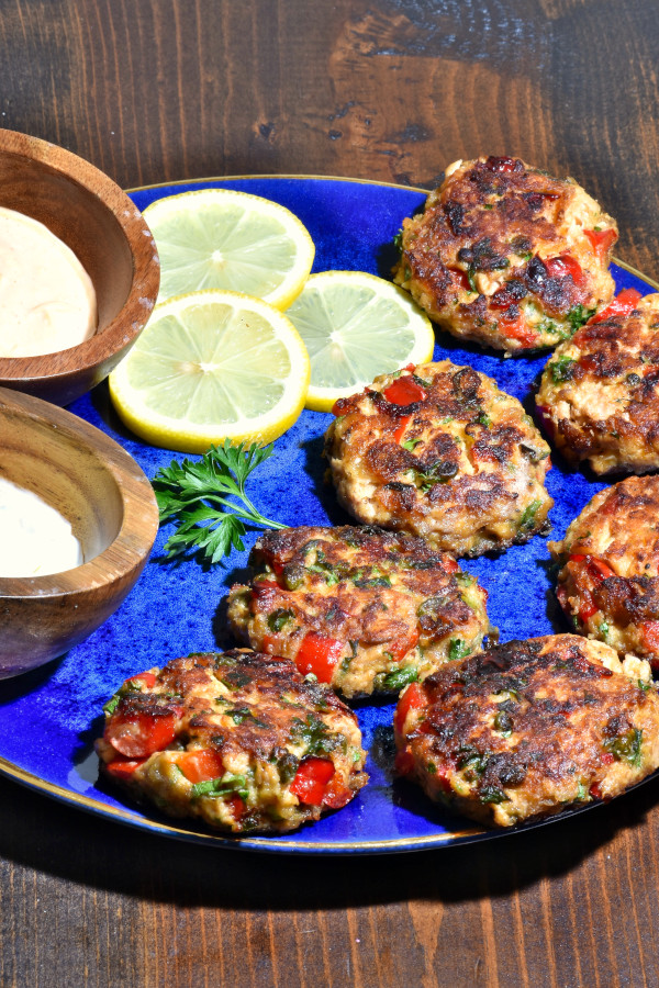 salmon patties on a blue plate with two different sauces