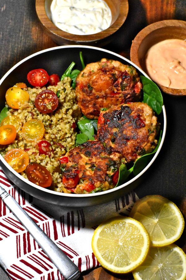 three salmon patties in a bowl with spinach and grains