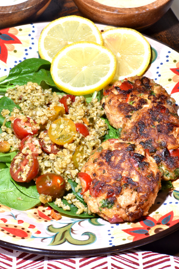 three salmon patties on the gypsy plate with spinach and grains