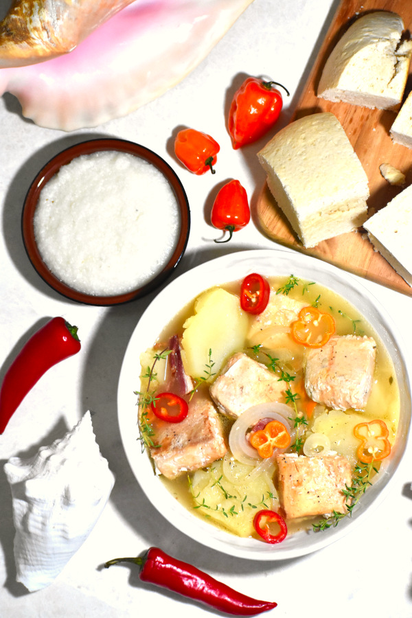 zoomed out image of a bowl of boiled fish alongside some johnny cake, grits and a few tropical shells