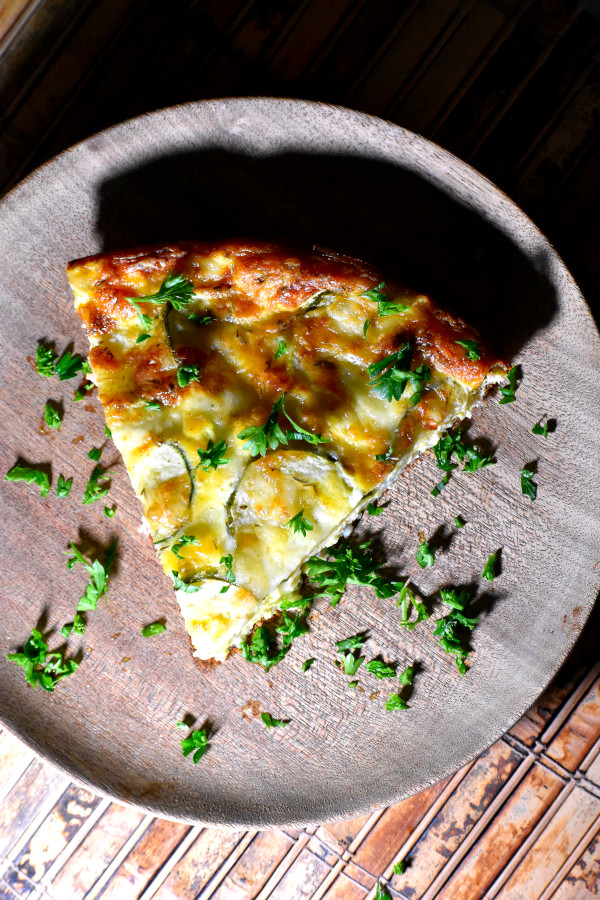 slice of quiche on a wooden plate