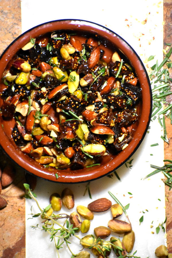 nuts, figs and honey mixed up in  a terra cotta bowl