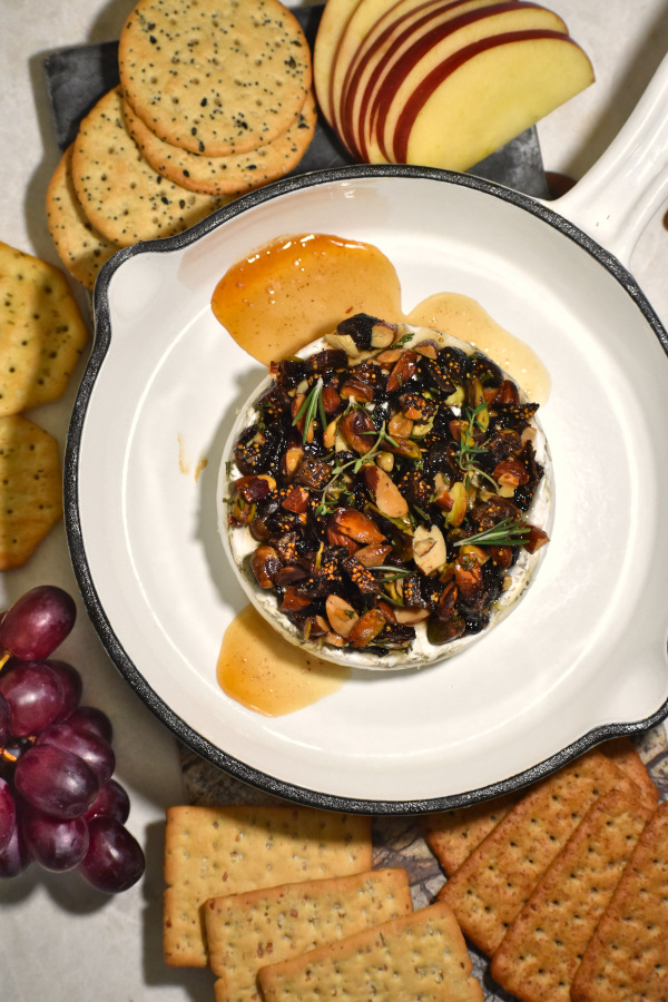 baked brie with nuts and honey in a small cast iron pan surrounded by crackers and fruit