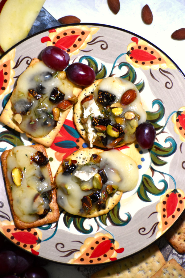 nice melty baked brie with toppings on four crackers on the gypsy plate