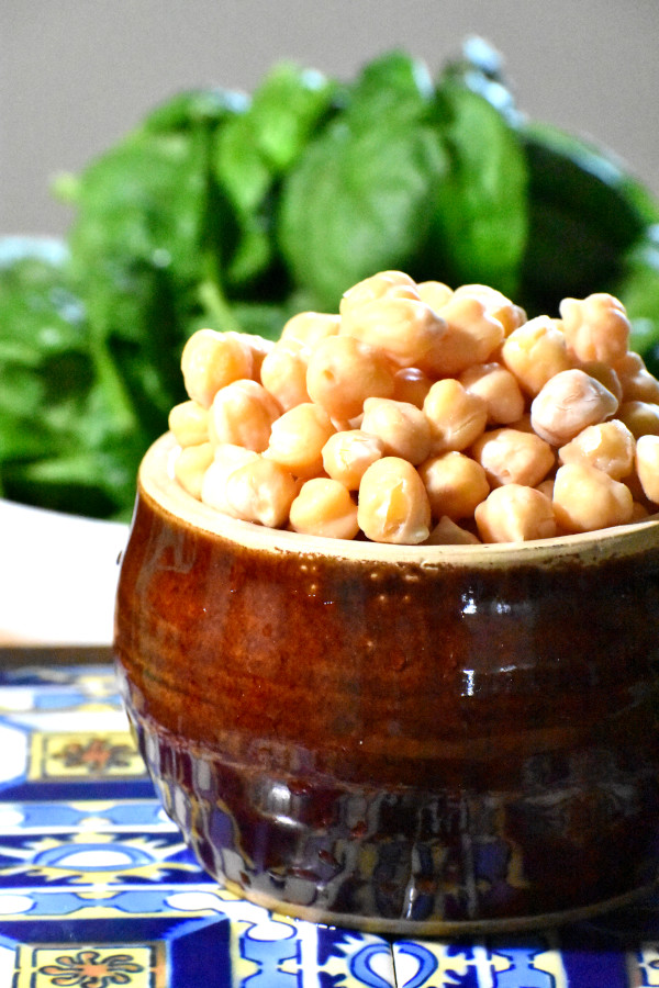 chick peas in a bowl with fresh spinach in the background