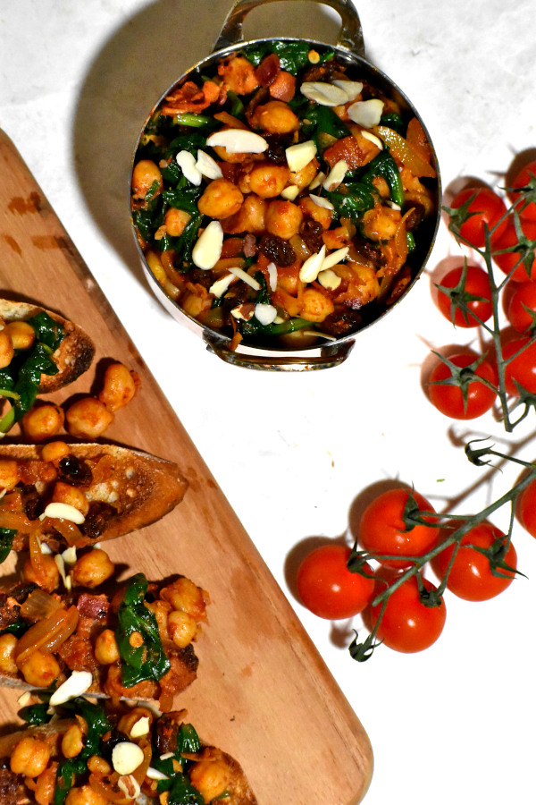 overhead shot of spanish chick peas with spinach in a bowl and alongside is some of the dish served on bread