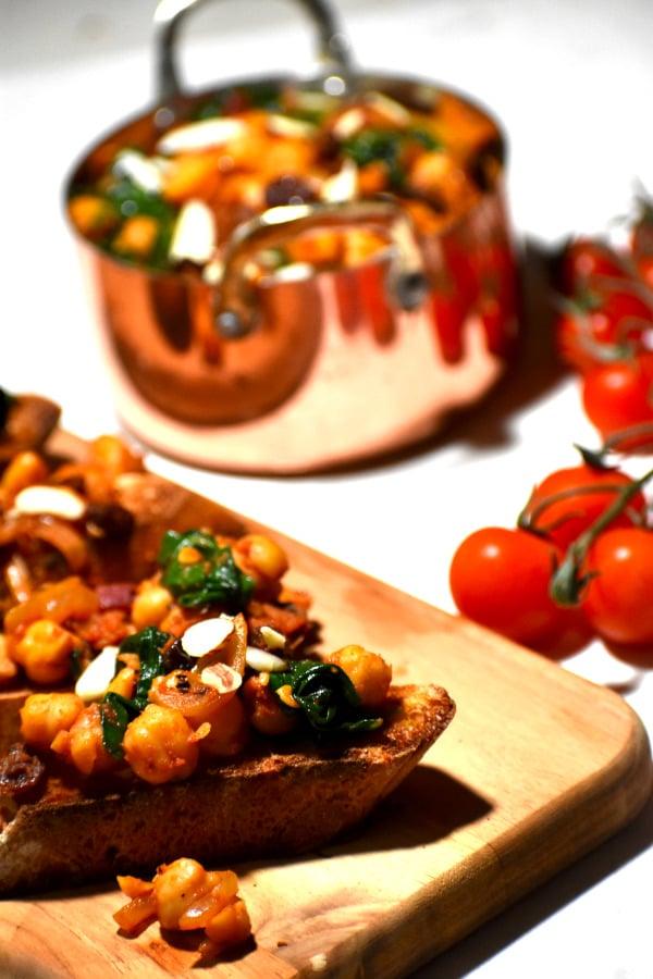 espinacas con garbazos on bread with a metal bowl in the background