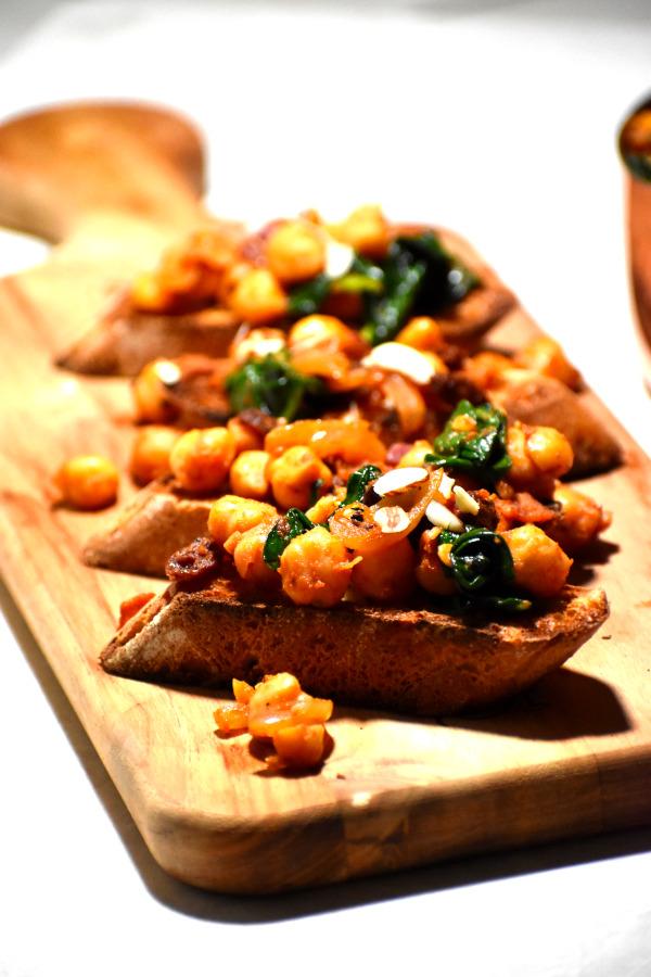 close up of espinacas con garbanzon served on crusty bread