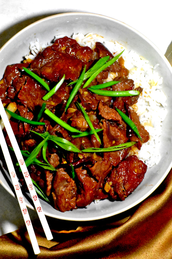 mongolian beef in a bowl over rice