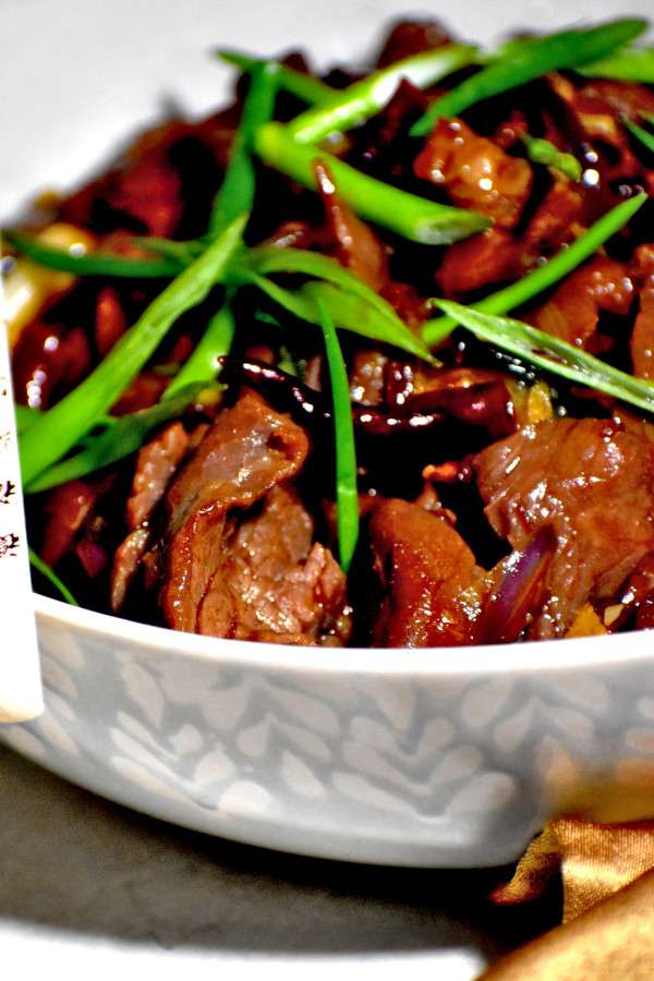 side view of mongolian beef in a white bowl