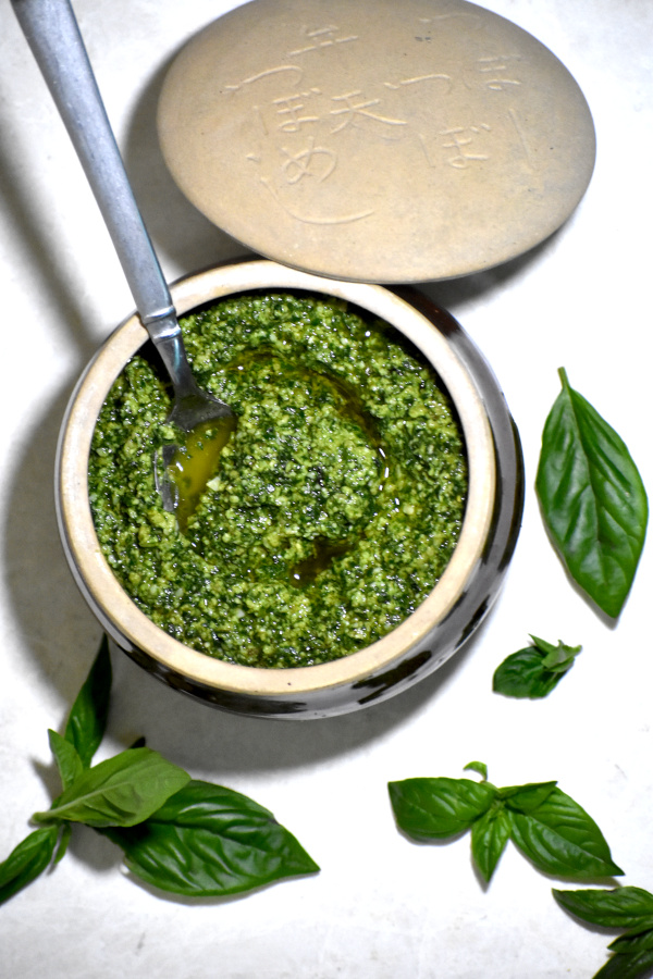 zoomed out image of bowl of pesto, surrounded by basil leaves