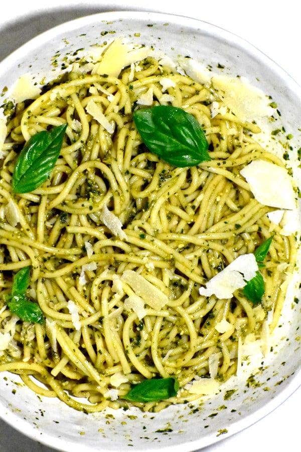 a bowl of pesto coated spaghetti noodles