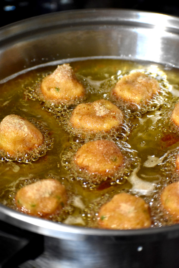 several balls sizzling in hot oil