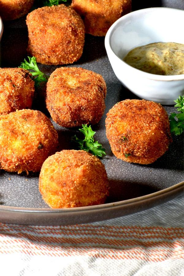 sauerkraut balls on a grey plate alongside a small dish of mustard.
