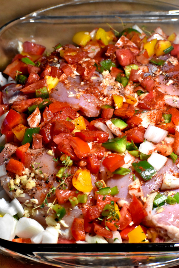 chicken marinating in the chopped vegetables and spices