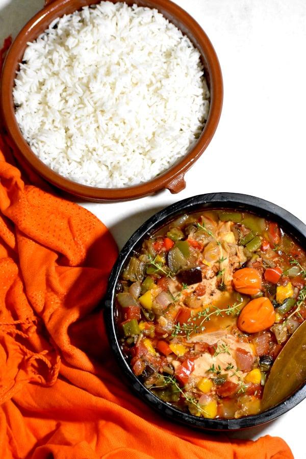 a bowlful of kedjenou chicken alongside a bowlful of rice