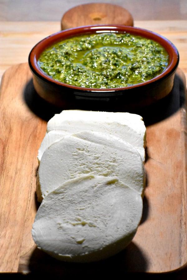 sliced mozzarella and a dish of pesto