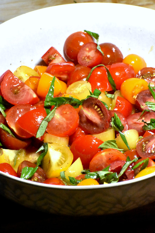 diced cherry tomatoes and strips of fresh basil in a bowl