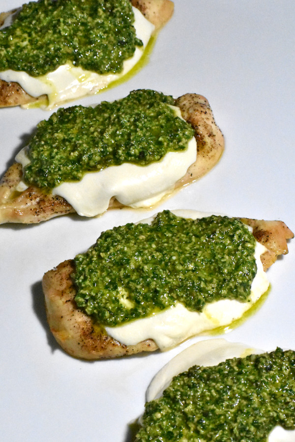 chicken cutlets topped with melted mozzarella and pesto sauce