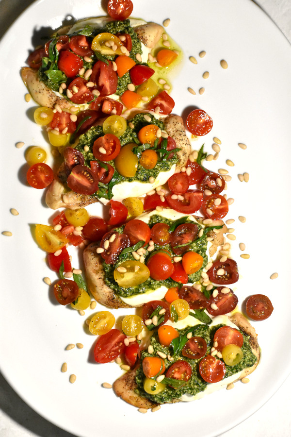 zoomed out picture of large platter with four chicken cutlets topped with pesto and bruschetta topping