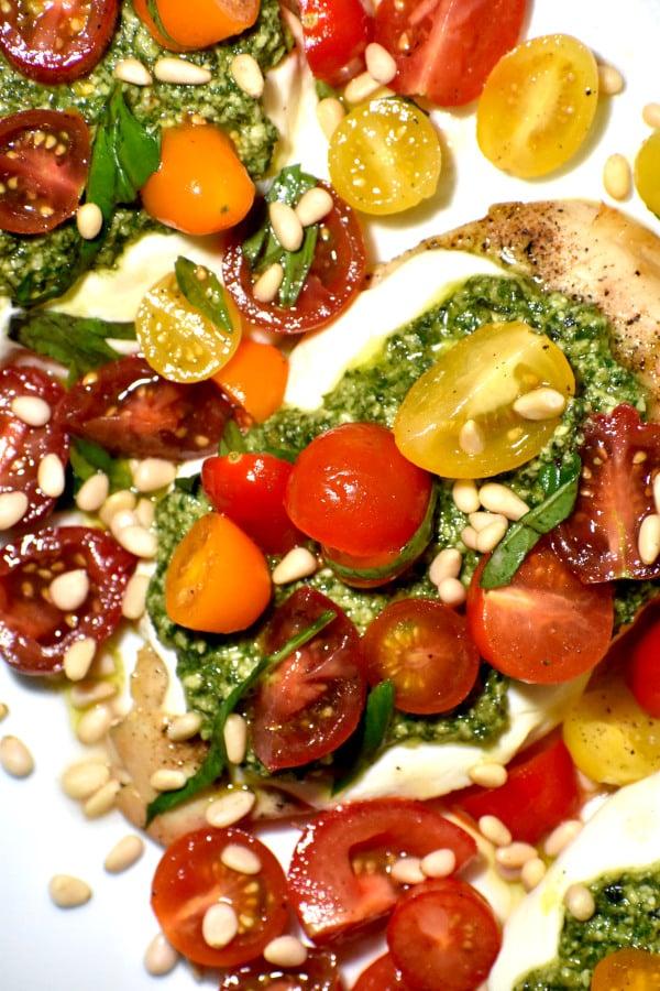 close up of pesto bruschetta topped chicken cutlet
