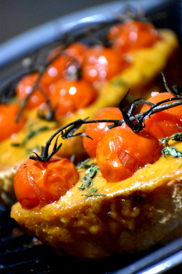 close up of welsh rarebit topped with roasted cherry tomatoes