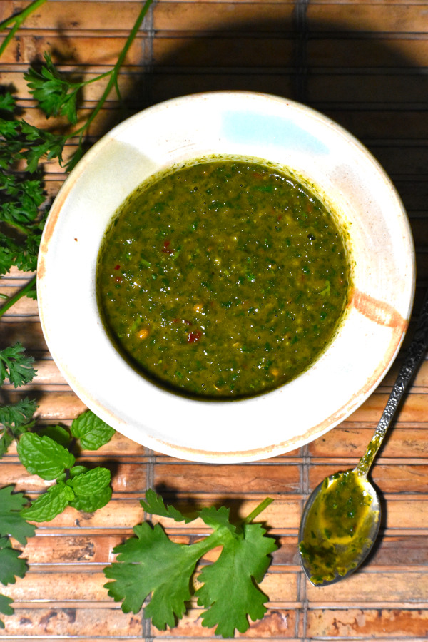 zoomed out picture of our bowl of chermoula alongside some fresh herbs