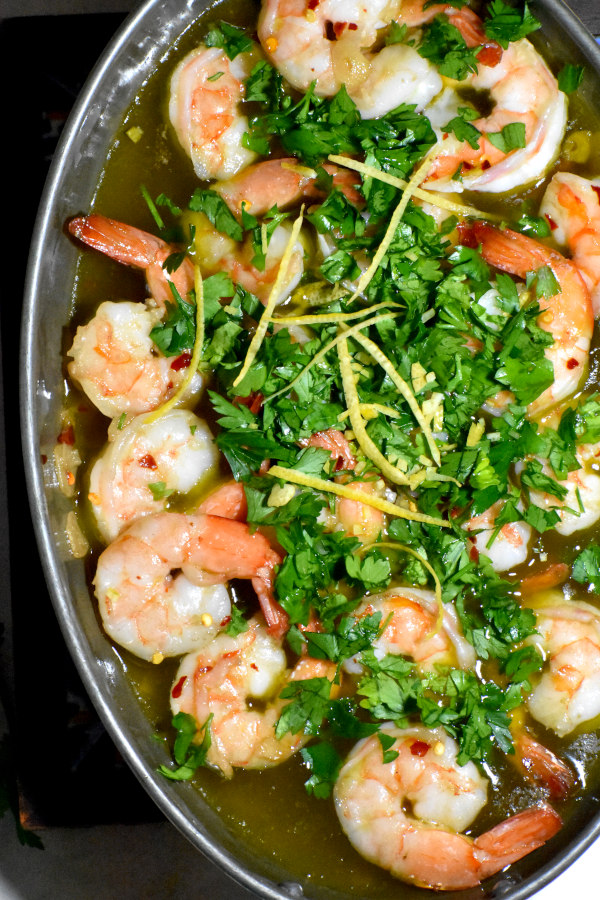Parsley and lemon zest added atop the cooked shrimp.