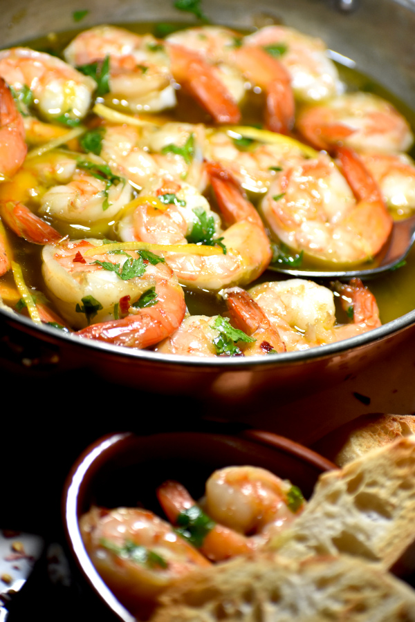 Side view of the pan full of gambas al ajillo with a smaller dish in the foreground.