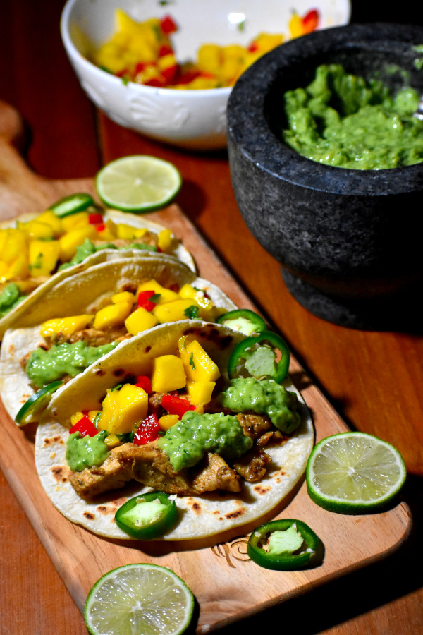three tacos topped with guasacaca