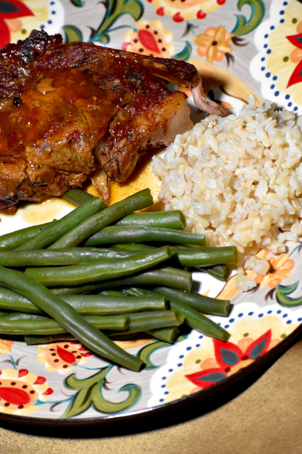 a melt in your mouth pork chop on the gypsy plate alongside brown rice and green beans