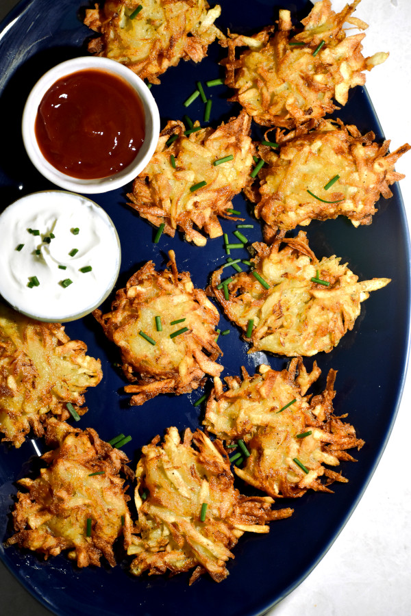 a bunch of potato latkes on a blue platter along with dipping sauce