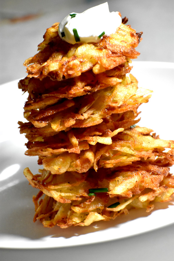 a big heaping stack of our latkes topped with a spoonful of sour cream