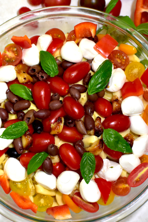 tomatoes, olives, mozzarella balls and roasted garlic atop the cooked tortellini