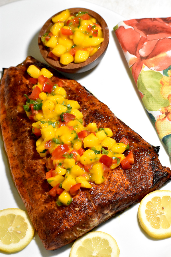 our mango salsa topped salmon with a bowl of extra mango salsa in the background