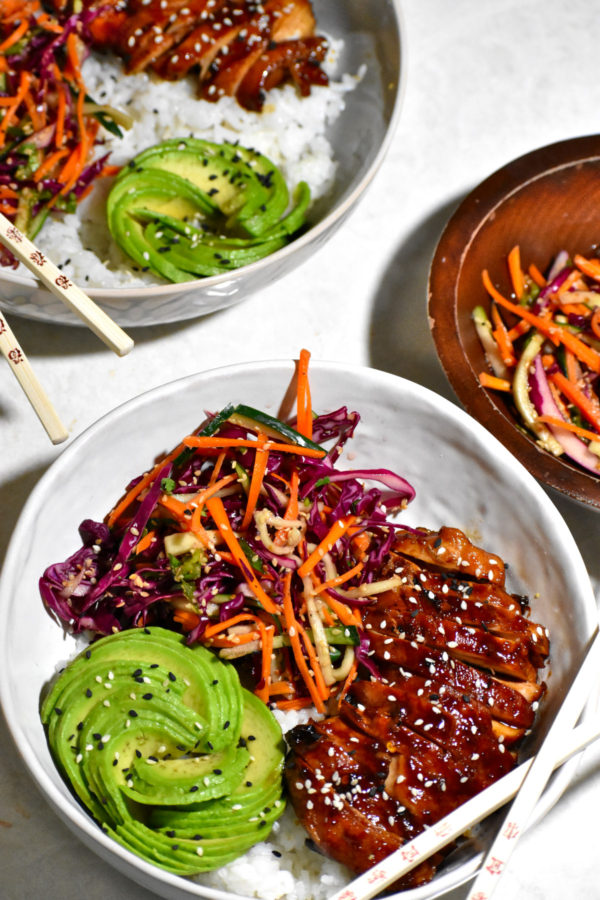 Two teriyaki chicken bowls, along with a small bowl of slaw, on a white background.