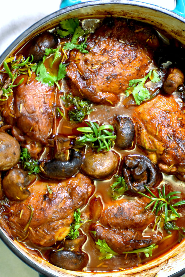 the pot of our braised chicken after coming out of the oven and garnished with more fresh herbs