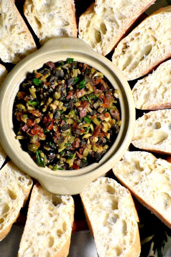 A small white bowl full of tapenade and surrounded by sliced baguette.